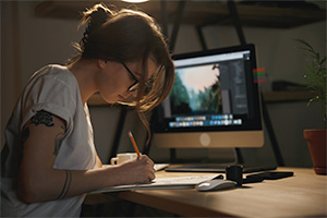 Woman drawing on a piece of paper with a computer in the background.